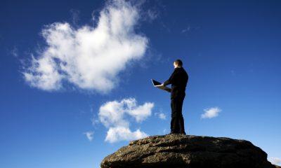 Mann på fjelltopp mot blå himmel