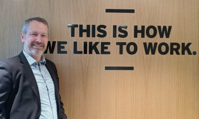 "Bilde av Kjetil Kalager foran vegg med ""This is how we like to work"""