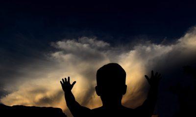 Silhuett mann strekker seg mot skyene